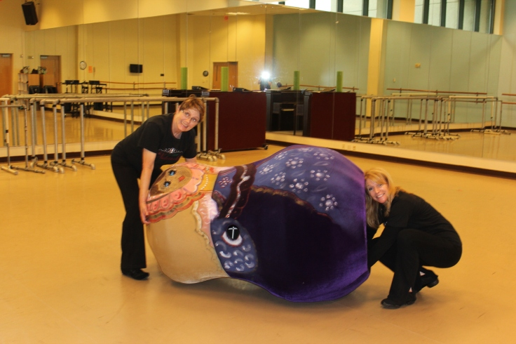 Valerie Hirvela assists Karen Heinemann into her Mother Matryoshka costume for rehearsal.