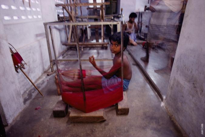 A ten-year-old boy winds thread on a loom in Kanchipuram.
